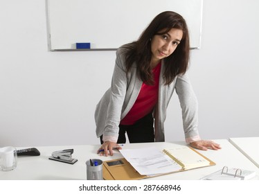 Middle aged businesswoman checking her agenda in the office