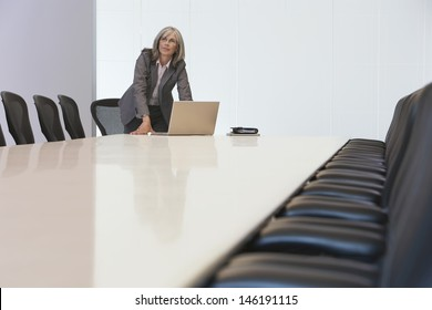 Middle aged businesswoman looking up by laptop in board room