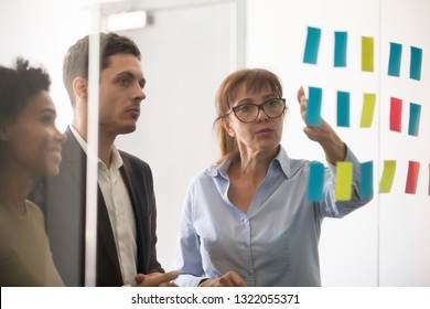 Middle aged businesswoman mentor coach leader explaining project strategy showing post it sticky notes on glass wall, serious business team brainstorm work plan at corporate office stand up meeting