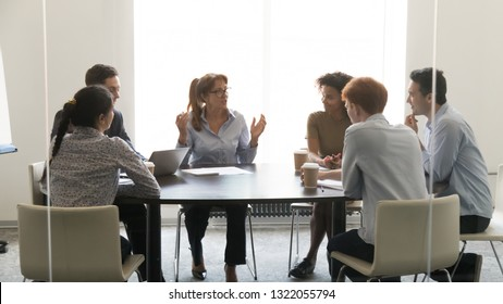 Middle aged businesswoman speaking at diverse group negotiations discussing work with colleagues, female executive talking to coworkers at corporate briefing sitting at conference table in boardroom
