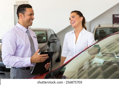 middle aged car salesman talking to a customer in showroom