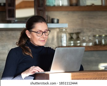 Middle aged caucasian businesswoman with glasses working at home - in the kitchen - with laptop. Stay home during covid-19 quarantine concept.