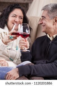 Middle aged Caucasian heterosexual couple relaxed, drinking red wine.