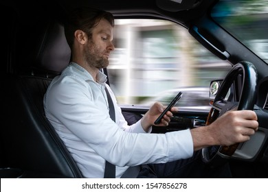A middle aged caucasian man distracted driving while using a mobile device.