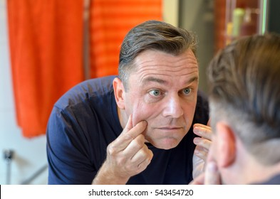 Middle aged caucasian man stands at mirror and pinches his face while wearing a blue shirt