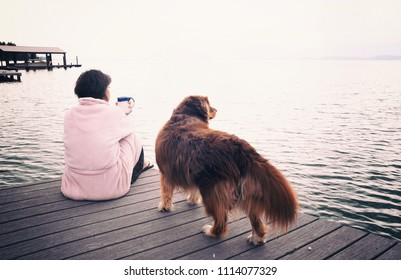 Middle aged caucasian woman and her dog sitting on lakeside dock drinking cup of coffee on a stormy mountain morning