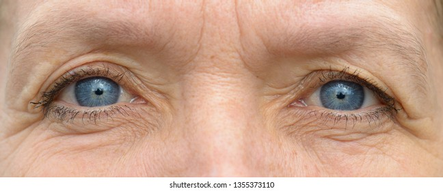 Middle aged caucasian woman with wrinkled face and pale blue eyes in close-up