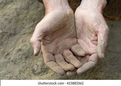 Middle aged Caucasion farmer man's dirty, empty hands in cupped or holding position on stone.