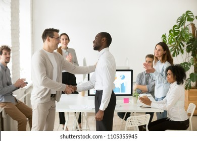 Middle aged CEO congratulating African American employee, shaking hand, tapping on shoulder, congratulating manager with promotion, welcoming new hired member of business team, colleagues applauding