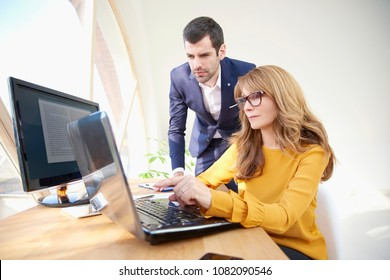 Middle aged confident businesswoman sitting at office desk in front of laptop while her young colleague standing next to her and working on financial report. Teamwork at the office.