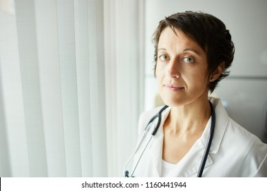 Middle aged confident female doctor in medical gown wearing stethoscope around her neck and looking at camera with tired eyes in soft daylight in hospital
