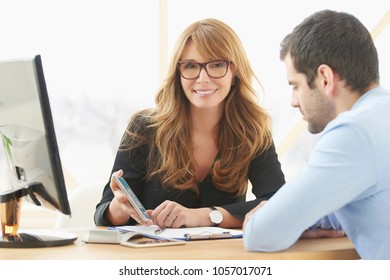 Middle aged consultant businesswoman sitting at desk and using mobile phone while consulting with young male business assistant  at the office.