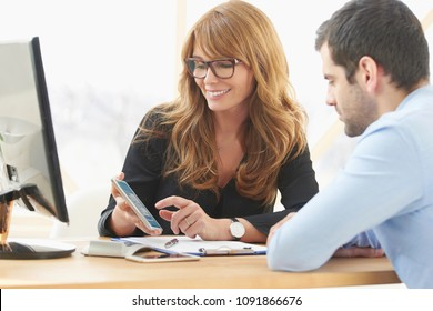 Middle aged consultant businesswoman sitting at desk and using mobile phone while consulting with young business assistant man at the office.