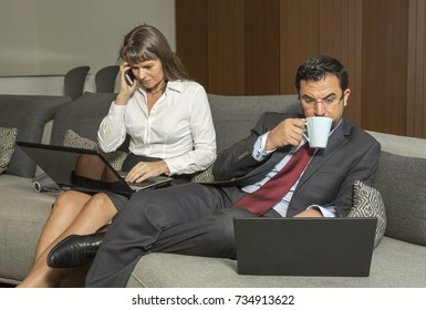 middle aged couple busy on their laptops and working from home, in formalware, having a coffee in their city apartment