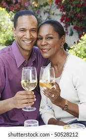 Middle aged couple celebrating with champagne, outdoors