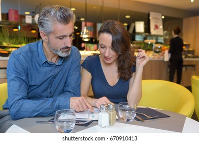 Middle aged couple choosing from restaurant menu