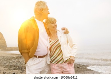 Middle aged couple enjoying the beach with lens flare