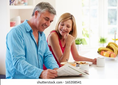 Middle Aged Couple Having Breakfast In Kitchen Together