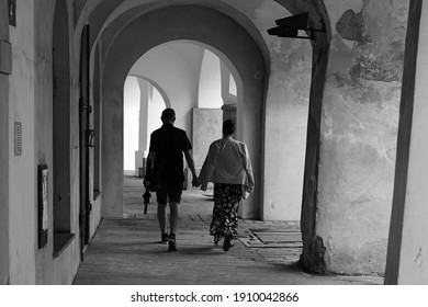 Middle aged couple holding hands walking in historic city arcade, black and white photo