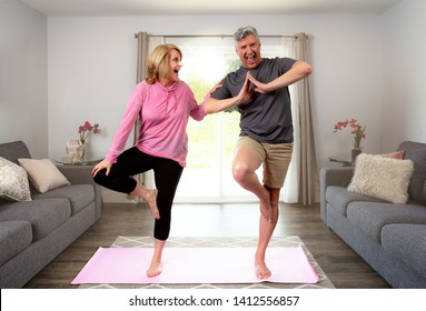 Middle aged couple laughing playful while self learning beginner yoga for better health, fitness, wellbeing, and healthy lifestyle