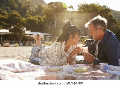 Middle aged couple lying on the beach making a toast, Ibiza