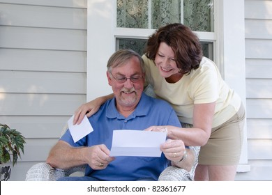 A middle aged couple reads a letter on the porch of their vintage house, enjoying reading good news together.