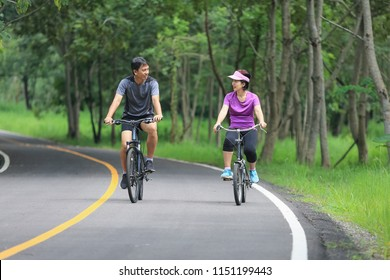 Middle aged couple relaxing exercise with bicycle in park