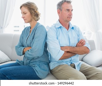 Middle aged couple sitting on the couch not speaking after a fight at home in the living room