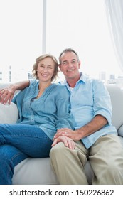 Middle aged couple sitting on the couch smiling at camera at home in the living room