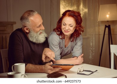 middle aged couple using digital tablet while sitting at table at home