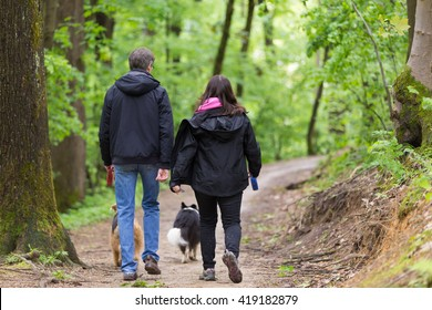 Middle aged couple walking their two dogs in forest.