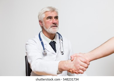 middle aged doctor with gray hair and beard making handshake
