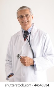 Middle aged doctor holding stethoscope over light gray background vertical composition torso only
