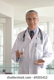 Middle aged Doctor in Labcoat with Pills and Glass of Water in modern medical facility. Vertical format.