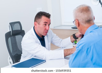 Middle aged doctor is showing his older patient ( senior ) his blood reading results on his laptop while sitting in his office.