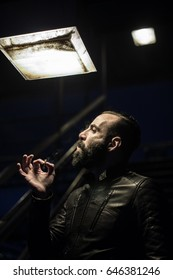 A middle aged, Egyptian man smokes in the streets of Brooklyn, New York City. He has a beard and is dressed in a leath jacket. Shot on a Spring night in 2017.