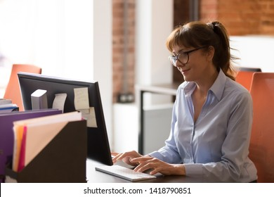 Middle aged employee businesswoman working typing on keyboard business e-mail looking at pc screen feels satisfied alone at modern shared coworking space. Solve matters distantly busy workday concept