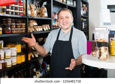 Middle aged european salesman working in delicatessen section of ordinary grocery