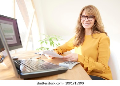 Middle aged executive businesswoman sitting at computer and laptop and doing some paperwork. Home office.