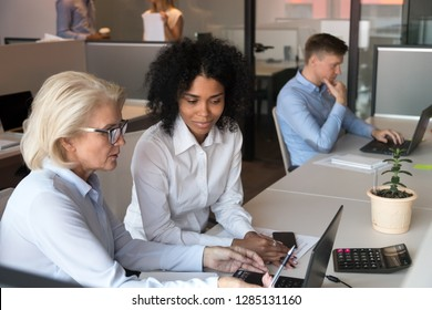 Middle aged experienced businesswoman company ceo helping to new employee afro millennial female with online task or corporate application useful program, fruitful teamwork of diverse workers concept