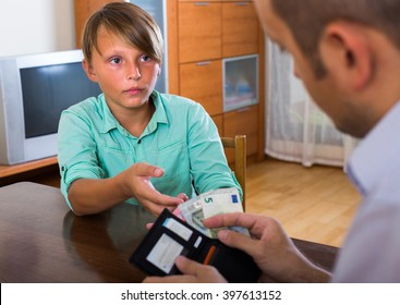 Middle aged father giving pocket money to teenage son