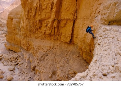 Middle aged female climber uses technique of the abseil method of roping down. Canyoning in dry wadi of Judaean desert, Israel