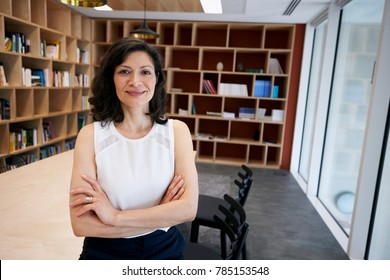 Middle aged female creative smiling to camera in her office