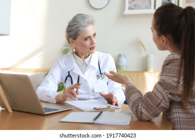 Middle aged female doctor therapist in consultation with patient in office