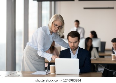 Middle aged female executive manager and male colleague working together in coworking space, businesswoman pointing on computer screen analyzing explaining business project results and discussing data