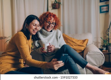middle aged female friends having fun at home, using mobile phone