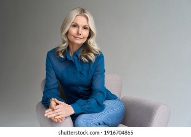 Middle aged female psychotherapist, counselor sitting in chair alone in office looking at camera. Sophisticated elegant mature 50s woman of mid age with blond hair posing indoors, portrait.