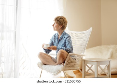 Middle aged female sitting on the armchair in front of curtains and looking at the view from a window. Pretty blond woman with short blond hair sitting in the morning and enjoying time with coffee.