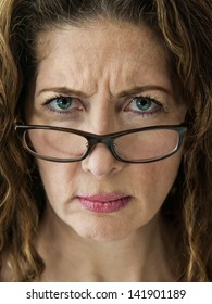 Middle aged female teacher frowning over her glasses.