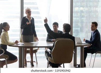 Middle aged female team leader stand listening to colleagues ideas at briefing, diverse employee brainstorm expressing thoughts to coworkers, negotiating at office business meeting. Teamwork concept